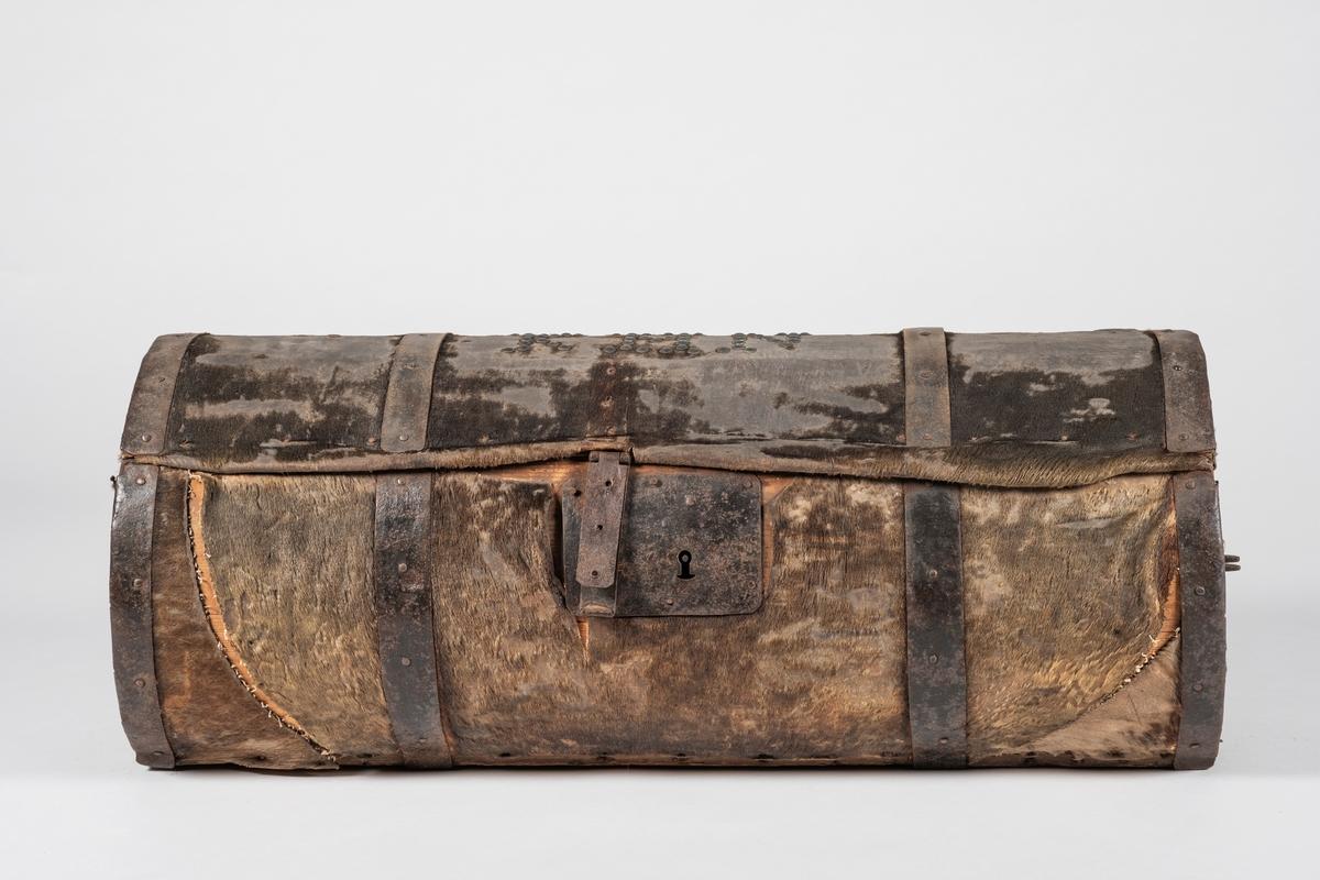 Sylindrisk reisekoffert, trukket med selskinn. Lokket er hengslet til bunnen med fire jernbeslag som følger rundt hele kofferten. Lås med jernbeslag, nøkkel mangler. Innside tredd med bomullslerret. Naglet på initsialer. Jernhåndtak på begge kortsider.