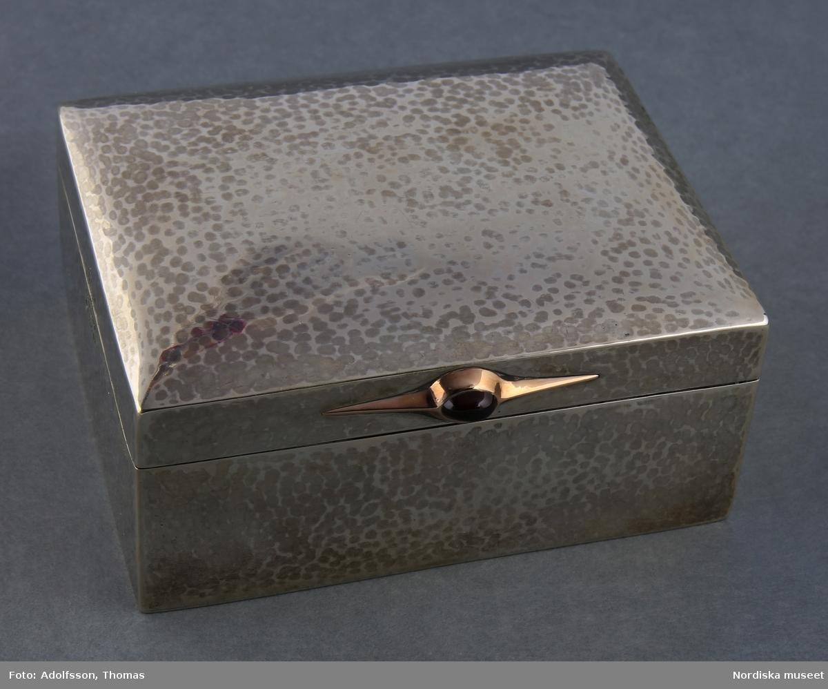 Skrin/ask, silver, rektangulär form.  Locket fast i asken medels gångjärn. Dekorerat med ett guldornament i form av en spetsig elipsform dekorerad med en röd sten/pärla. Asken är invändigt klädd med träfaner.  Stämplad C.G Hallberg, ortstämpel för Stockholm, kontrollstämplar; kattfot och S inom sexkant, årstämpel Q7.   /Cecilia Wallquist 2019-01-31