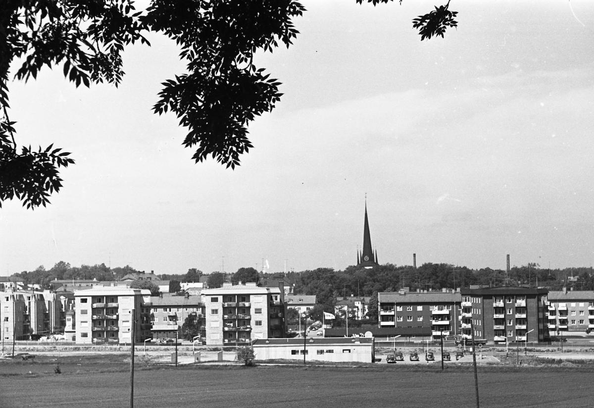 Utsikt från Brattberget. En bensinstation. Höghusen vid Munkgatan. Tornet på Heliga Trefaldighetskyrkan.