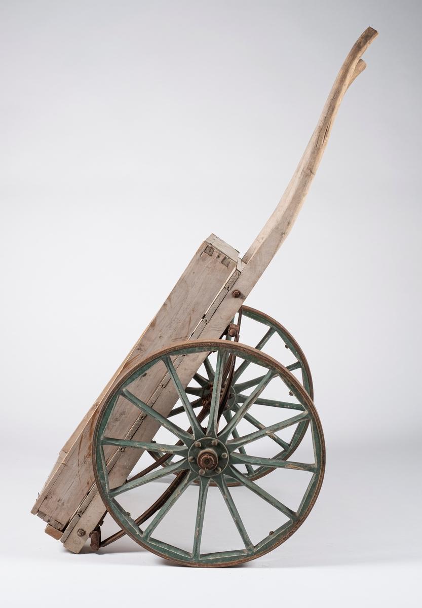 Håndkjerre på to hjul, dannet av et plan med og to lange håndtak. Stangen mellom hjulene er skrudd til to buede metallstenger som er skrudd på rammen under planet.  Løs karm ligger oppå.