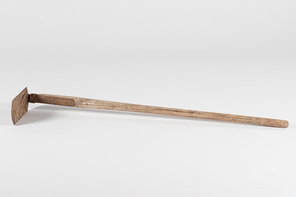 Kraftig treskaft med en rett jernplate festet vinkelrett nederst på skaftet.
