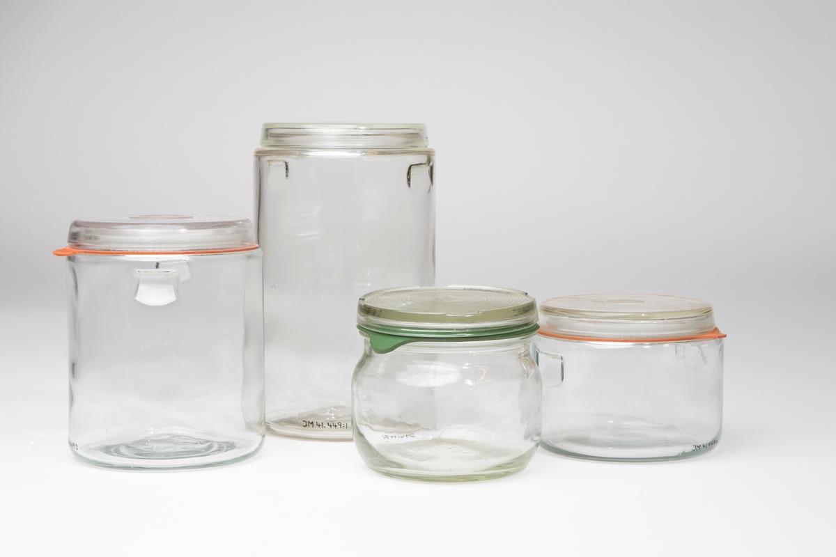Konserveringsglas, 4 stycken, bestående av glasburk, glaslock, gummiring och metallbygel. Metallbygeln håller ihop burk, lock och gummiring vid sterilisering i vanlig gryta (i en konserveringsapparat finns särskilda klämmor/fjädrar, som håller fast burkarna i innerställningen). Burkarna hör till konserveringsapparat 41448:1-12.  JM 41449:1-4, Glasburkar med lock JM 41449:5-8, Gummiringar, 2 st oranga, 2 st gröna JM 41449:9-12, Metallbyglar, 4 st