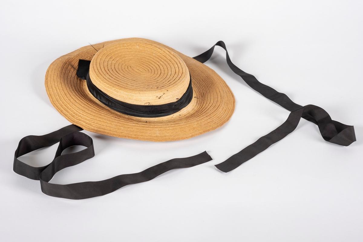 Naturfarget, oval stråhatt med sort pyntebånd rundt pullen. Undersiden av bremmen er fòret med fløyel. Under fòret er bremmen stivet av med en ståltråd. Hvit og blåstripet svettebånd av bomull. Svart hakerem.