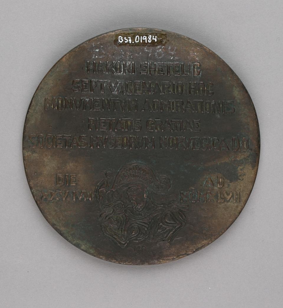 Minneplate med relieff av Haakon Shetelig (forside) og tekst samt mannshode med uniformshatt  (bakside).