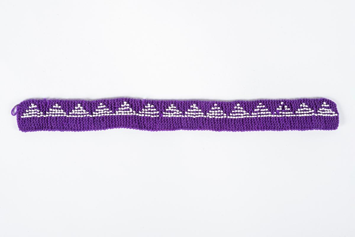 Lilla strikket bånd med perlebroderi.