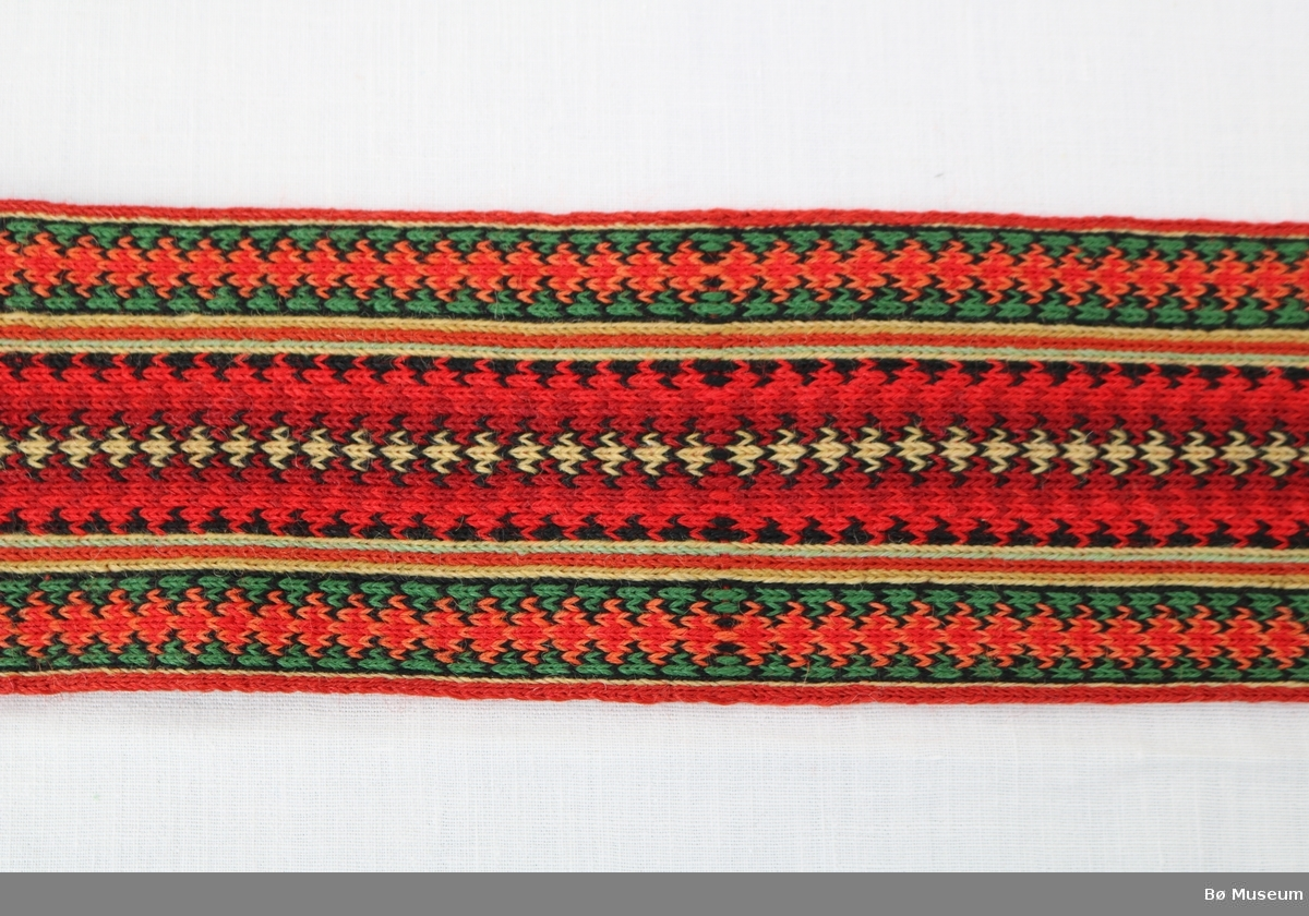 Brikkebelte (a) og hårband (b) med tradisjonelt mønster. Beltet har trykknapper, hekter til lukking og frynse i den eine sida.