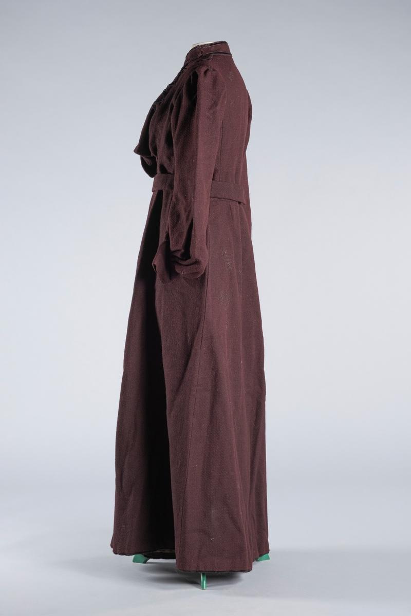 Todelt lilla kjole bestående av kjoleliv og skjørt, samt et belte.   Kjoleliv i ull, ballongermer,  puff øverst ved skulder. I ryggen er det sydd inn fem spiler. Tre av spilene er sydd fast med metallisk tråd, mens to av dem er sydd direkte inn i foret. På innsiden av livet, i hver skulder, er det sydd fast en tøyhempe. Innvendig er livet fôret med grått bomullstoff, men i halsen er det brukt hvitt stoff. Innvendig kan fôret lukkes med hekter i front. I hver side av fôret er det to rader med hemper og hekter annenhver gang. Foran er jakken posete nederst, og med en bredere klaff i en side. Klaffen legges over det sammenhektede innerfôret, og festes med to hekter i den ene siden kjolelivet. . Halslinningen er bred, har ikke lukking foran, men har en lenger klaff som festets til tøyhemper i siden av halsen. Kjolelivet er pyntet med to rader velourbånd rundt halsen, samt nedover fronten av livet. I hver side, loddrett over brystet, er det velourbånd som danner 4 kryss, i alt 8 stykker. Nederst i kjolelivet er det 8 hekter for feste av livet til skjørtet.   Skjørt i ull. På innsiden av livet er det 8 små metallhemper jevnt fordelt, for å feste skjørt og kjoleliv sammen. Det er også to større hemper av stoff i hver side av skjørtelinningen. I skjørtelinningen er det en splitt for på-og avkledning. I splitten er det sydd inn 5 hekter, og disse festet i 5 hemper av tråd på utsiden av skjørtet. Midjevidden kan reguleres med en hekte på innsiden av linningen, som kan festes i en av to vannrette hekter på utsiden. Skjørtet har en brun lomme på innsiden for oppbevaring. Nederst på innsiden av skjørtet er det en bred fôret kant, en forsterkningskant, med et påsydd svart bånd.   Lilla belte i ull med bomullsfôr på innsiden. Det er sydd på tre metallhekter i den ene enden. Et hekte er festet på innsiden av foret, og to stykker i bredden nedenfor. Disse to hektene er sannsynligvis festet i etterkant da de er sydd fast i foret. For feste av beltet er det sydd fast to små metallhemp
