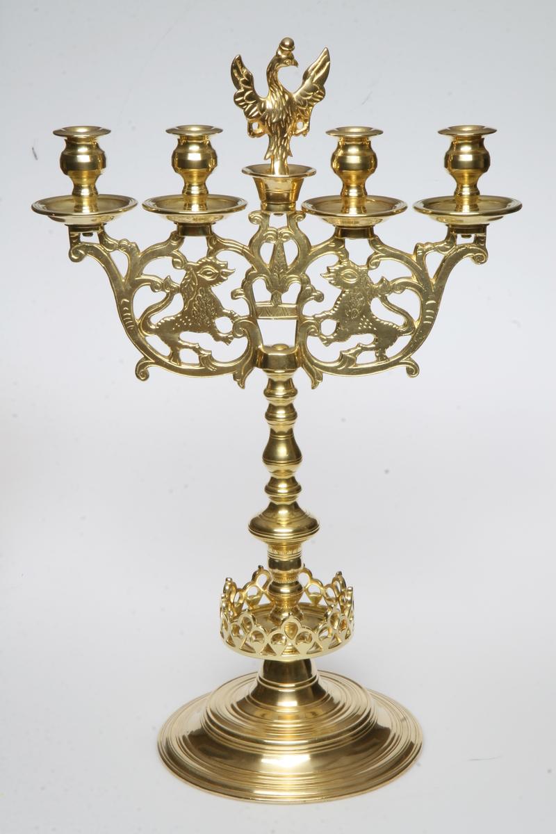 Toarmet, fire lysholdere. Balusterformet stolpe, gjennombrutt krans rundt stolpens nedre del. Armene gjennombrutt og siselert: ranker og to motstilte løver. Midt mellom lysholderne en ørn med sverd og septer i klørne. Lik AS.310684.
