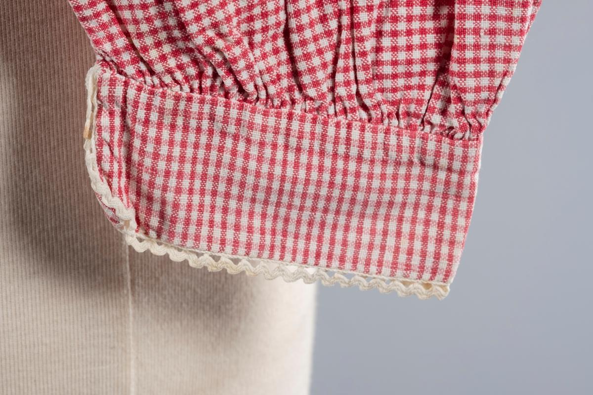Rød og hvit rutete nattrøye i bomull med puff- og ballongermer. Den har blondekanter på kragen og mansjettene. På mansjettene er det perlemorsknapper. Trøyen har en høy krage. Det er sydd folder bak ved kragen og øverst på ermene. Trøyen har åpning i front og lukkes med én perlemorsknapp i kragen.