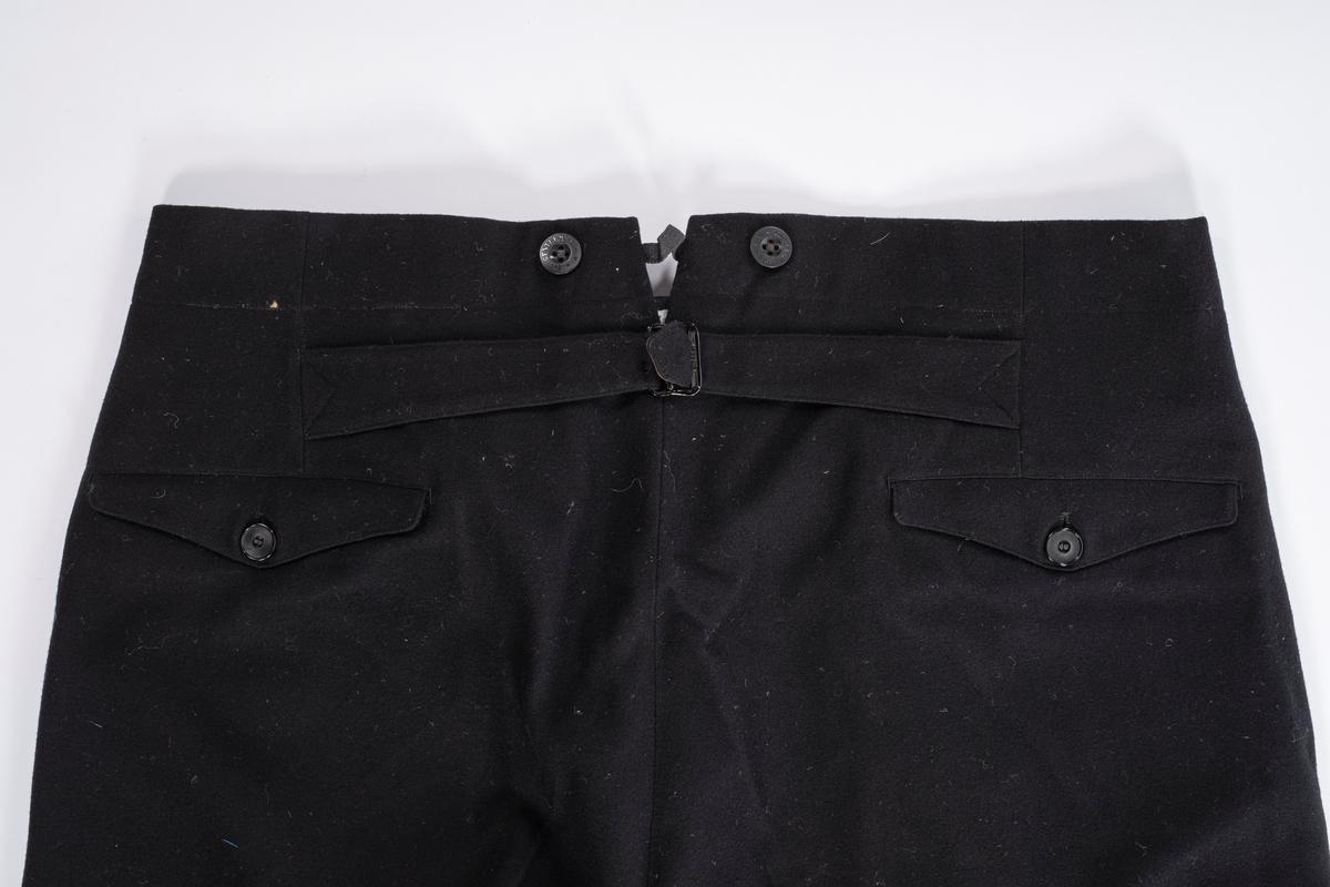 Svart bukse med spensel bak og knapper til bukseseler. Den har sidelommer og baklommer. Den lukkes i front med knapper.