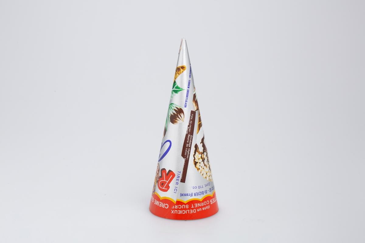 En iskrem i kjeks toppet med sjokolade og hasselnøttstrø. Hasselnøttplante med tre hasselnøtter. Ansikt av et barn som har på seg en krone.