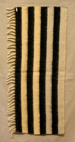 Vävprov till pläd vävd i inslagsförstärkt kypert. Vävprovet är oliksidigt. På ena sidan är det 50 mm breda ränder i svart och vitt. På den andra sidan är det enfärgat, först gult och sedan blått i 200 mm vardera. I både varp och inslag är det stickgarn extra 8/2. Varpen är enfärgad vit. Det är en 70 mm lång vit drejad frans i ena sidan och vit, troligen virkad, kant i den andra.   Vävprov till pläd med modellnamn Randnar är formgivet av Ann-Mari Nilsson och tillverkat av Länshemslöjden Skaraborg. Det finns med  på sidan 60-61 i vävboken Inredningsvävar av Ann-Mari Nilsson i samarbete med Länshemslöjden Skaraborg från 1987, ICA Bokförlag. Se även inv.nr. 0001-0024,0026-0040.  Vävprovet är kemtvättat efter nedsotning i en brand i Slöjdens Hus augusti 2000.