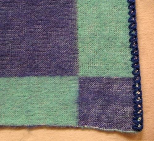 Vävprov till filt vävd i inslagsförstärkt tuskaft i smidig halvylle kvalitet. Det är blekt tvåtrådigt bomullsgarn i varpen och blått (blålila) och blågrönt (turkost) tvåtrådigt ullgarn, filtgarn, i inslaget. Filten är dubbelsidig. På ena sidan dominerar den blålila färgen och den turkosa bildar en ram och tvärt om på andra sidan.  Den ena långsidan är virkad med blålila garn och den andra med turkost. Vävprovet är märkt med R28:2 på ett vitt bomullsband.  Se även inv.nr 0028:1 Filt Dubbel.  Vävprov till filt med modellnamn Dubbel är formgivet av Ann-Mari Nilsson och tillverkat av Länshemslöjden Skaraborg. Det finns med  på sidan 66-67 i vävboken Inredningsvävar av Ann-Mari Nilsson i samarbete med Länshemslöjden Skaraborg från 1987, ICA Bokförlag. Se även inv.nr. 0001-0027,0029-0040.