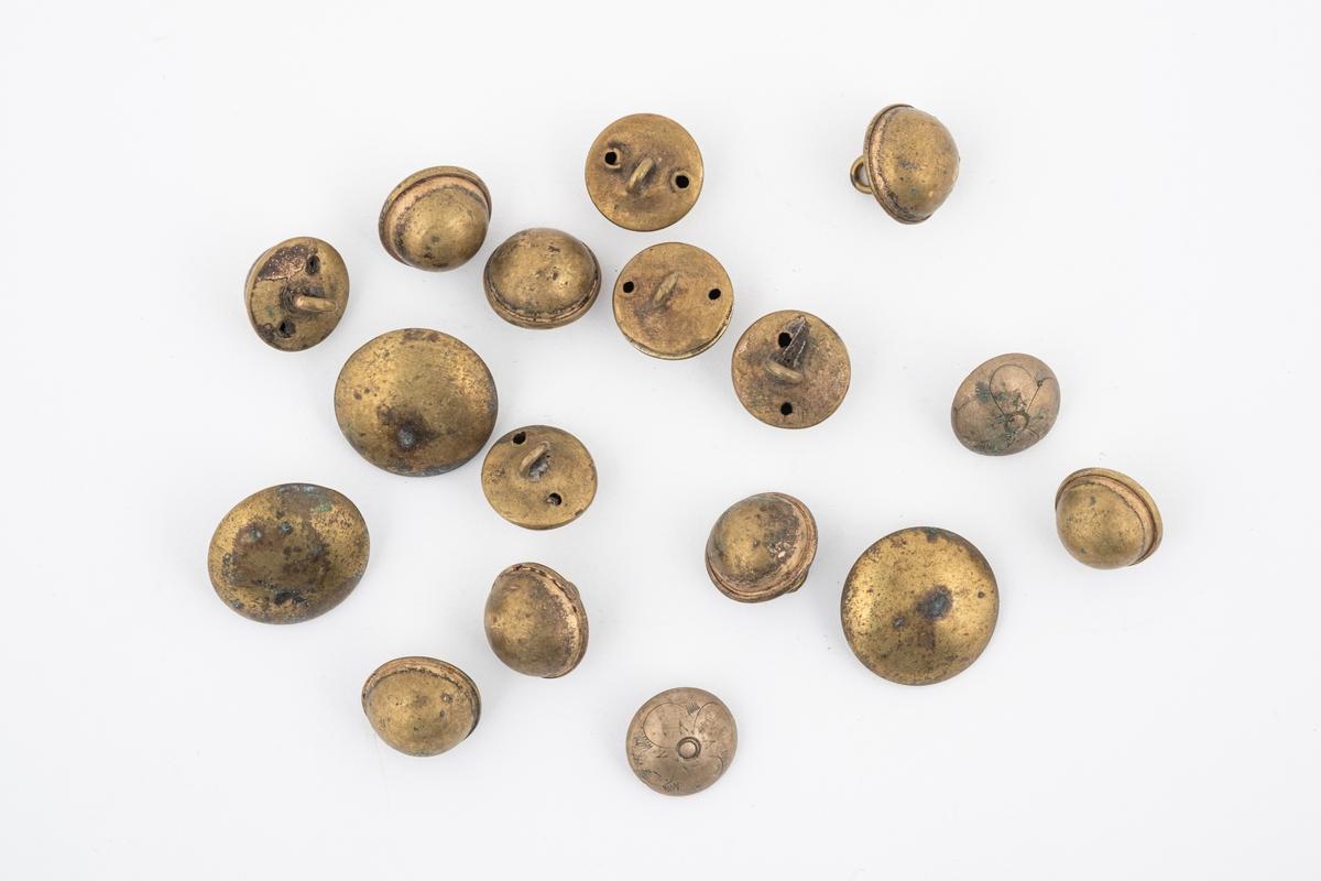 17 runde øyeknapper i tre forskjellige former. Knappene er i messing. 2 av de har inngravert blomstemønster, 3 av de er store og flate og de 12 siste er små og dype/høye.