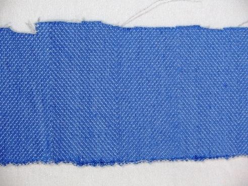 """Vävprov till möbeltyg. Ett kraftigt och stelt möbeltyg vävt i kypert med inslagseffekt. Varpen är av ljust grått tvåtrådigt bomullsgarn. Inslaget är entrådigt blått lingarn tre trådar tillsammans. Möbeltyget ger ett randigt intryck då man växlar mellan högerlutning och vänsterlutning var femte cm. Se även inv.nr. 0023:1-3 Möbelöverdrag, möbeltyg monterat på stolsdyna.   Vävprovet med modellnamn Fåra är formgivet av Ann-Mari Nilsson och tillverkat av Länshemslöjden Skaraborg. Det finns med  på sidan 56-57 i vävboken """"Inredningsvävar"""" av Ann-Mari Nilsson i samarbete med Länshemslöjden Skaraborg från 1987, ICA Bokförlag. Se även inv.nr. 0001-0022,0024-0040."""
