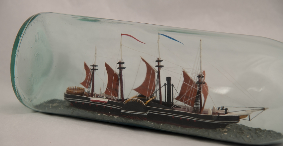 """Flaskeskute: Hjuldamperen """"Great Western"""".  Glass , klart , svakt grønnlig.  Knop rund munnningen , med rød lakk.  Sortmalt skrog, rødbrunt dekk og rødbrune seil , firemastet.  """"Great Western"""""""" var nr. 2 i den transatlantiske fart , Sirius var den første i 1838. """"Great Western ,"""" var konstruert av Isambard Kingdom Brunel , fikk 46 overfarter."""