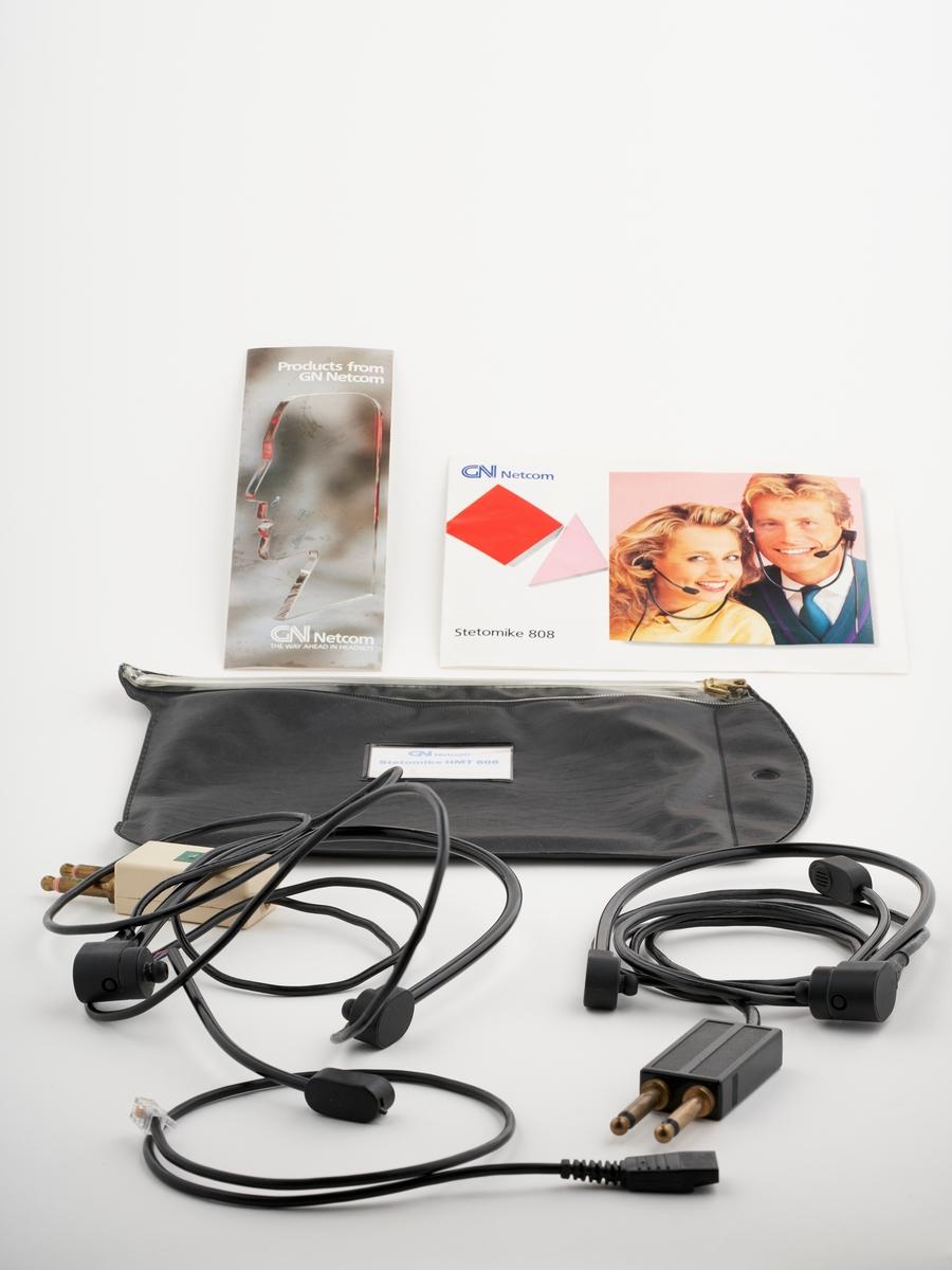 En oppbevaringspose med to hodetelefoner, to bruksanvisninger og en kabel.  NAV-samlingen er en gruppe av gjenstander som har vært anvendt på sosialkontoret (Aetat - NAV) i Skedsmo kommune.