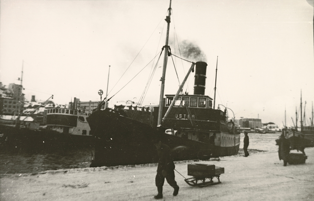 Motivet viser DS OSTER (bygget 1908) til kais ved Bryggen i Bergen. Mann med varer på kjelke i forgrunnen.