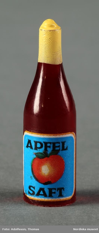 Tio flaskor som ska föreställa saft, drinkmix samt vin och sprit. Flaskorna är i olika färger som a-d) rött (4 st), e-h) gult (4 st) och i-j) grönt (2 st) och har små etiketter av papper. Hör till dockskåpsinredningen i matkällaren till dockskåp NM.0331721+.