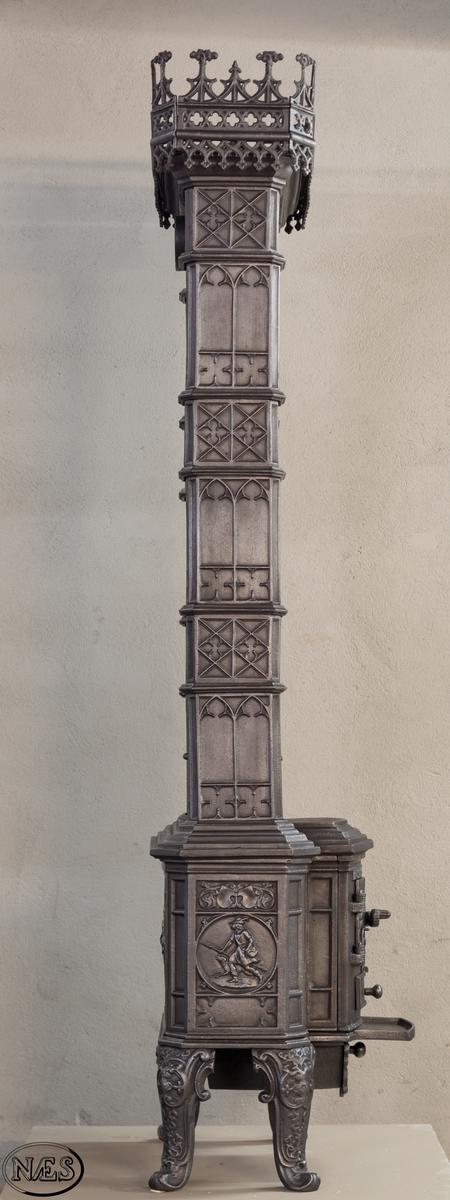 Etasjeovn med jernbein. Ilegg på langside gjennom liten dobbel-dør. På kortsidene jeger med hund i rund medaljong. Over brennkammeret er ovnen bygget opp etasjevis av liggende kasser og stående rør med gotiske detaljer. Hver etasje har to gitterverksdører, foran og bak, med engel og barn på ryggen. Ovnen avsluttes med krans på toppen.