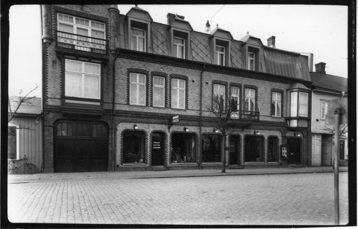 1906 lät sadelmakare E Malmgren uppföra huset. I vindsvåningen hade Sia Dahlbergs sin fotoateljé med fönster åt gatan. (Häftet kv. Kyrkan. Prästgården med flera).  På affärsskylten kan man läsa A/B Malmgrensmöbler, Foto Ateljér.