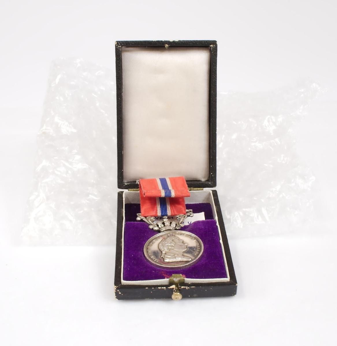 """Sølvmedalje med bånd i de norske nasjonalfargene. Den ene siden bærer kong Carl Johans portrett, og den andre siden har ordene """"For borgerdåd"""" omkranset av eikekrans. Hempen har kronedekor. Medaljen oppbevares i originalt etui."""