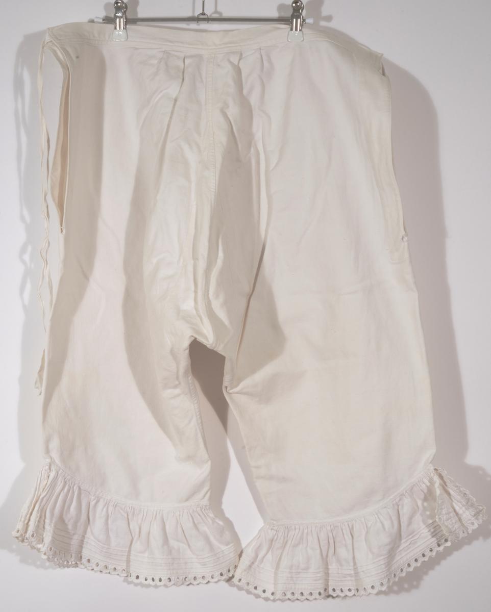 Hvit underbukse av bomull med halvlange ben. Hjemmesydd. Rysjer med biser og håndsydd blonde nederst på kanten. Knyting på hver side av livet. Lukket i skrittet. Kile for å få inn fasong - eller fordi stoffet ikke var bredere.