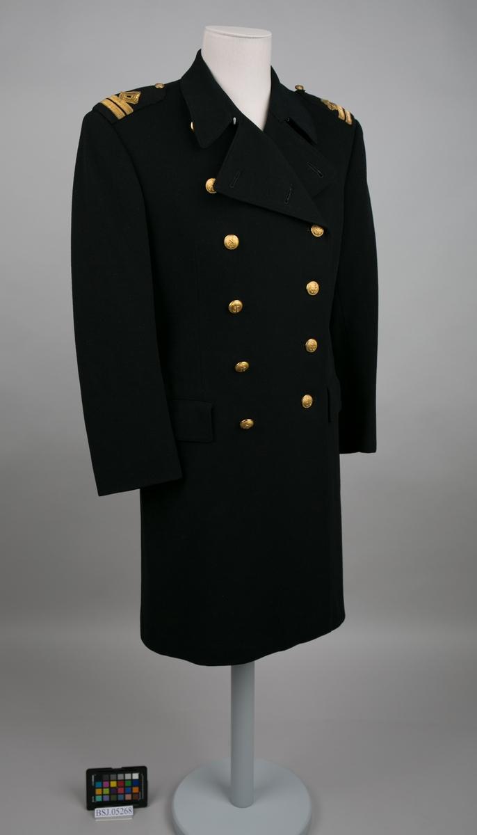 Førstestyrmann uniformsfrakk med distinksjoner på hver skulderputer. Dobbelspent med til sammen 12 stk. knapper i gullfarge med motiv av anker (en mangler).