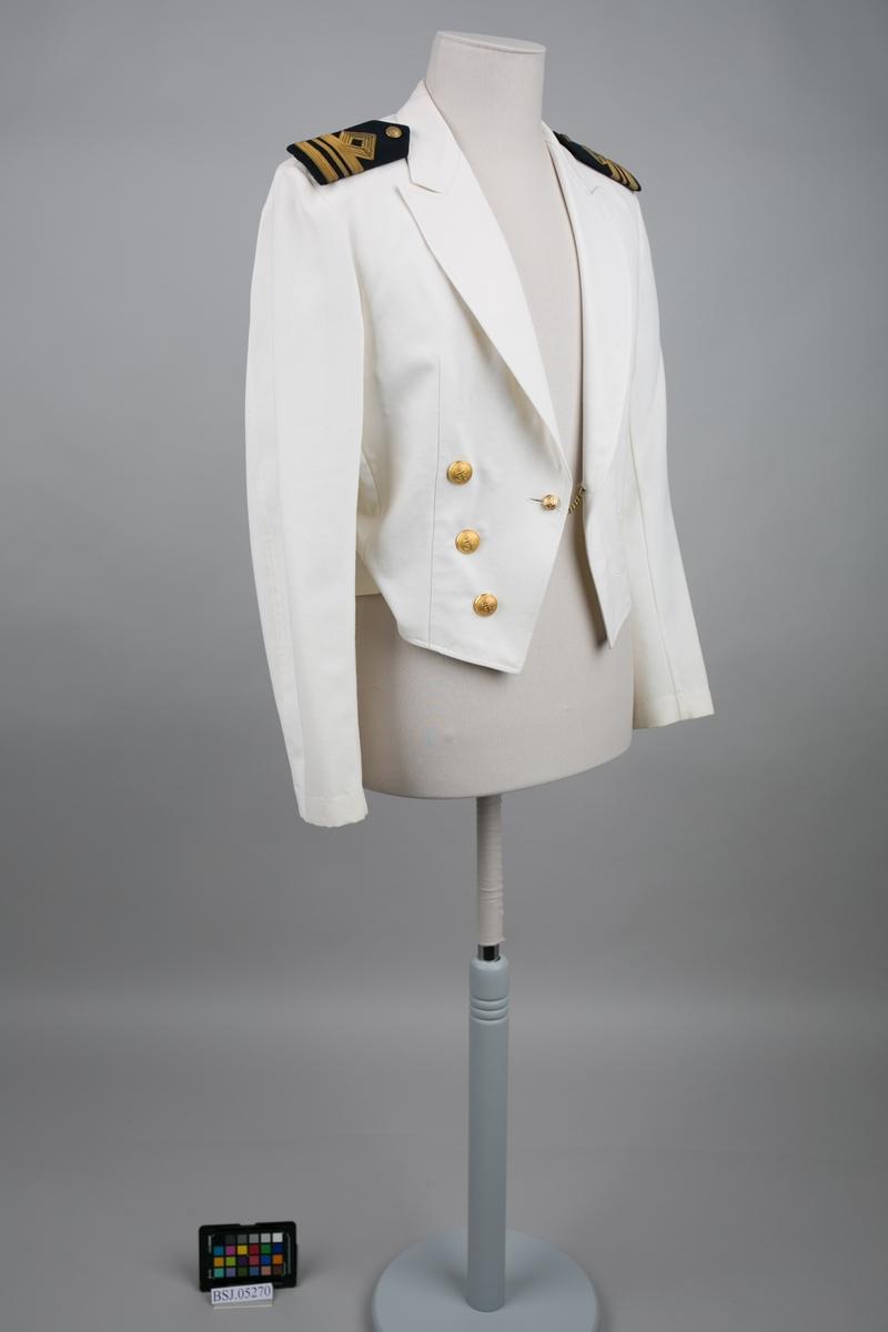 Styrmannsjakke tropeuniform med 3 stk. gullbånd og påmonterte distinksjoner på skulder. Dobbelspent med til sammen 3 stk. store knapper og 2 små knapper i gullfarge med emblem av anker.