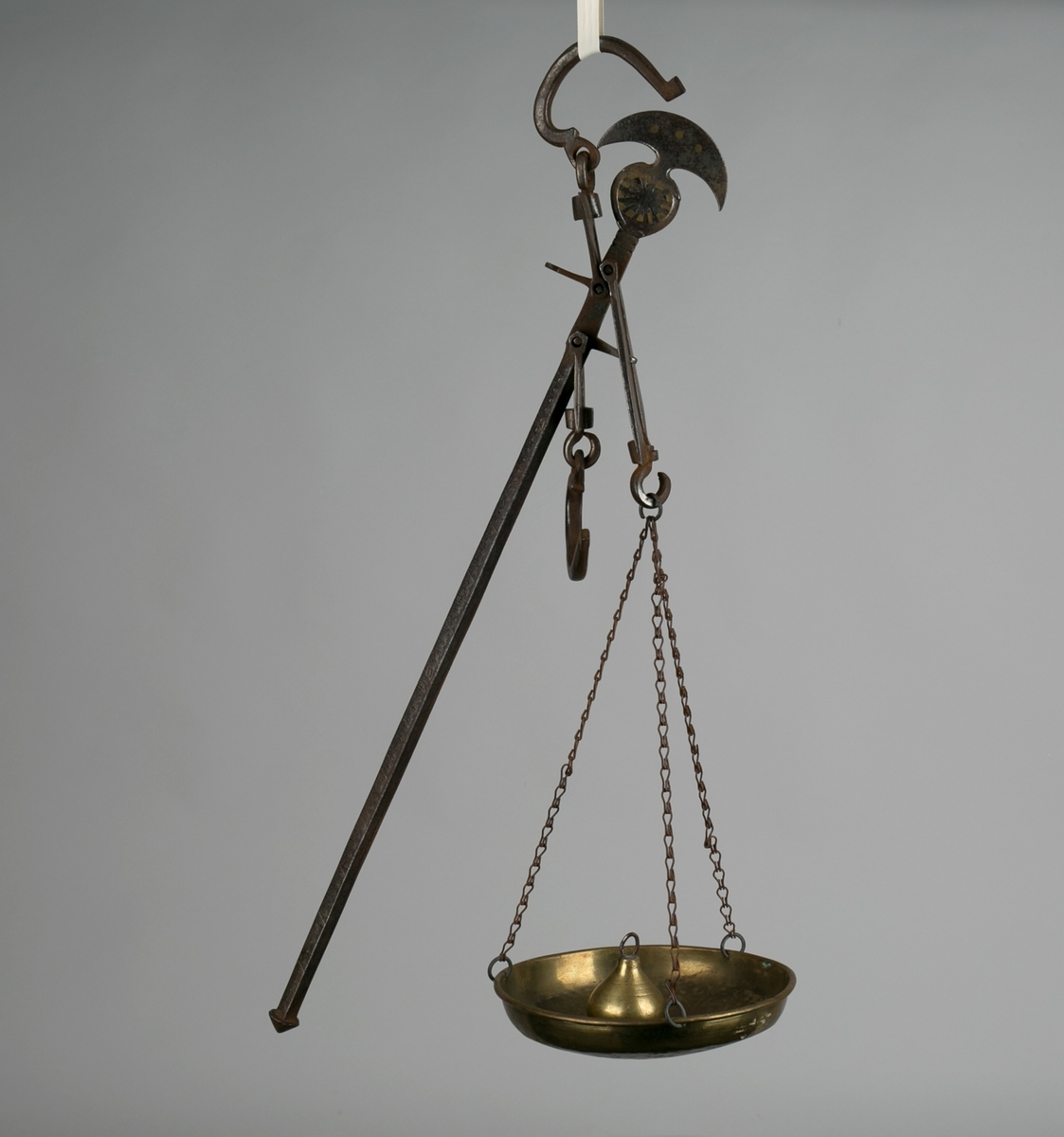 Bismervekt med dekor i ene ende - av jern med lodd, kroker og vektskål. Vektstang med skala. Vekten henger etter krok, mens loddet skyves til balansen er funnet.