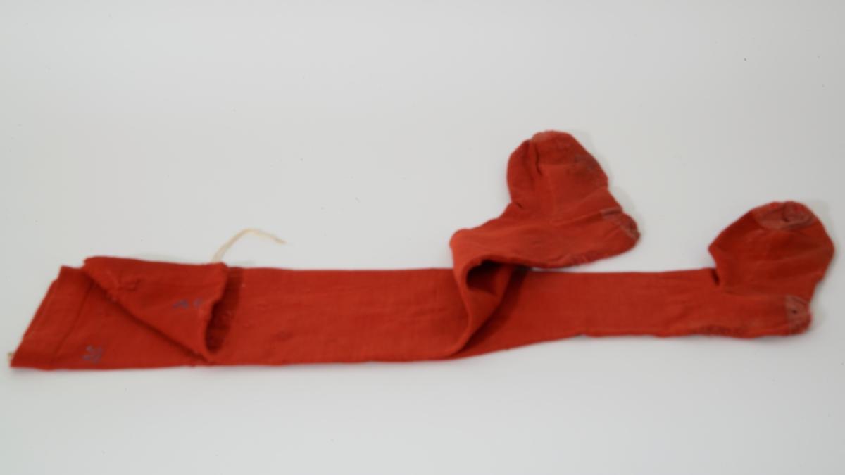 Røde ullstrømper med søm og nedbrettet overkant. Stoppet. 14 cm lang påsydde bendelbånd i øvre kant.