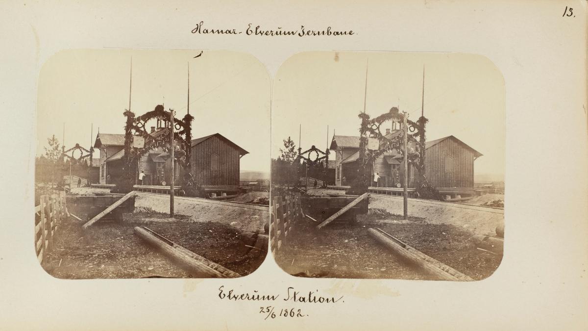 Elverum stasjon med blomsterportaler i anledning den høytidelige åpningen av strekningen Hamar-Elverum 23.06.1862, to dager før bildet ble tatt