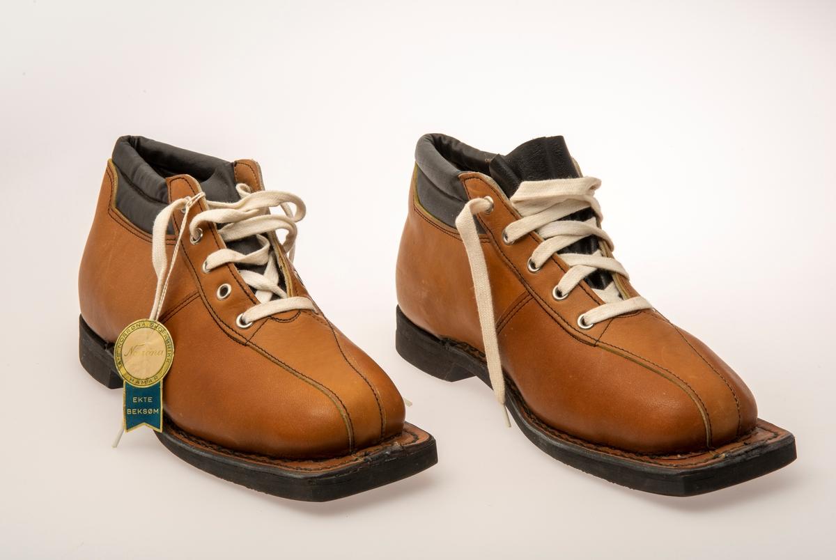 Skisko/Beksøm, lys brune med sort ankelstøtte. Sort gummisåle. Hvite skolisser. Hull til rottefellebindinger. Størrelse 41.