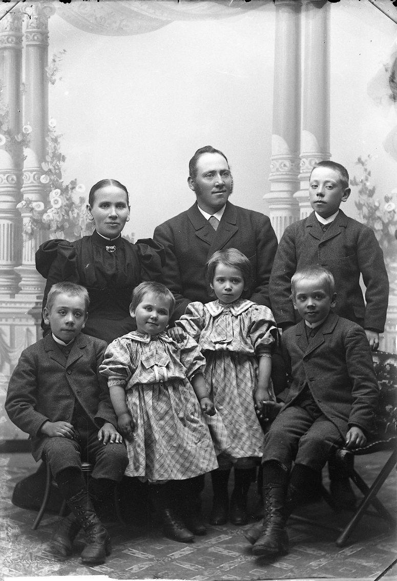 Familjen Ernst Andersson i Fattarp: föräldrar med två flickor och tre pojkar. Sittande i bakre raden är Karolina Andersson och maken Ernst Andersson. Äldsta sonen Gustav står intill. Sittande i främre raden är David, Elisabet, Edit och Erik.