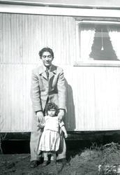 En ung man står tillsammans med en liten flicka framför en b