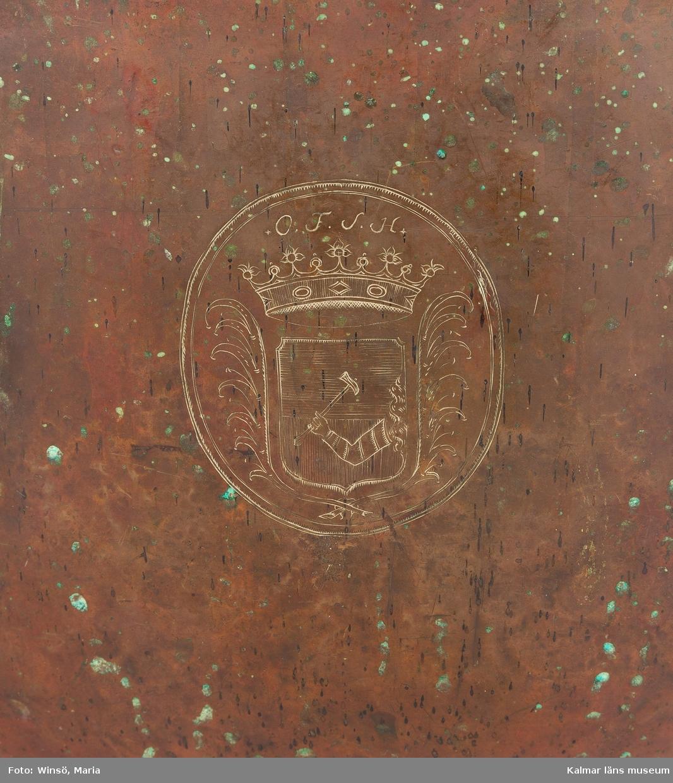 KLM 14939. Puka. Av koppar med beslag av järn och skinn på ovansidan. Står på tre korta ben formade som öglor. På utsidan skruvar och beslag formade som tulpaner. Försedd med Stålhammarska vapnet. Par med KLM 14940.