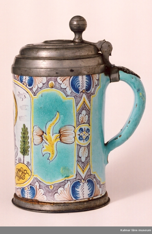 KLM 1710  Krus av fajans. Sejdel med hänkel och tennlock. . Fajans i blått, violett, gult och grönt. Motiv med naken kvinna som svänger gul schal i luften, hon omges av två gröna träd, hon står på en bevingad gul kula som omges av två gula dekorationer. Tennlock med lockmedalj, som består av ett infält mynt av kejsar Frans I, manshuvud i profil, runt om finns text: FRANCISCUS I.D.G. ROM. IMP. SEMP. AVG. Tumgrepp: kula med gördel. Tennskodd botten.