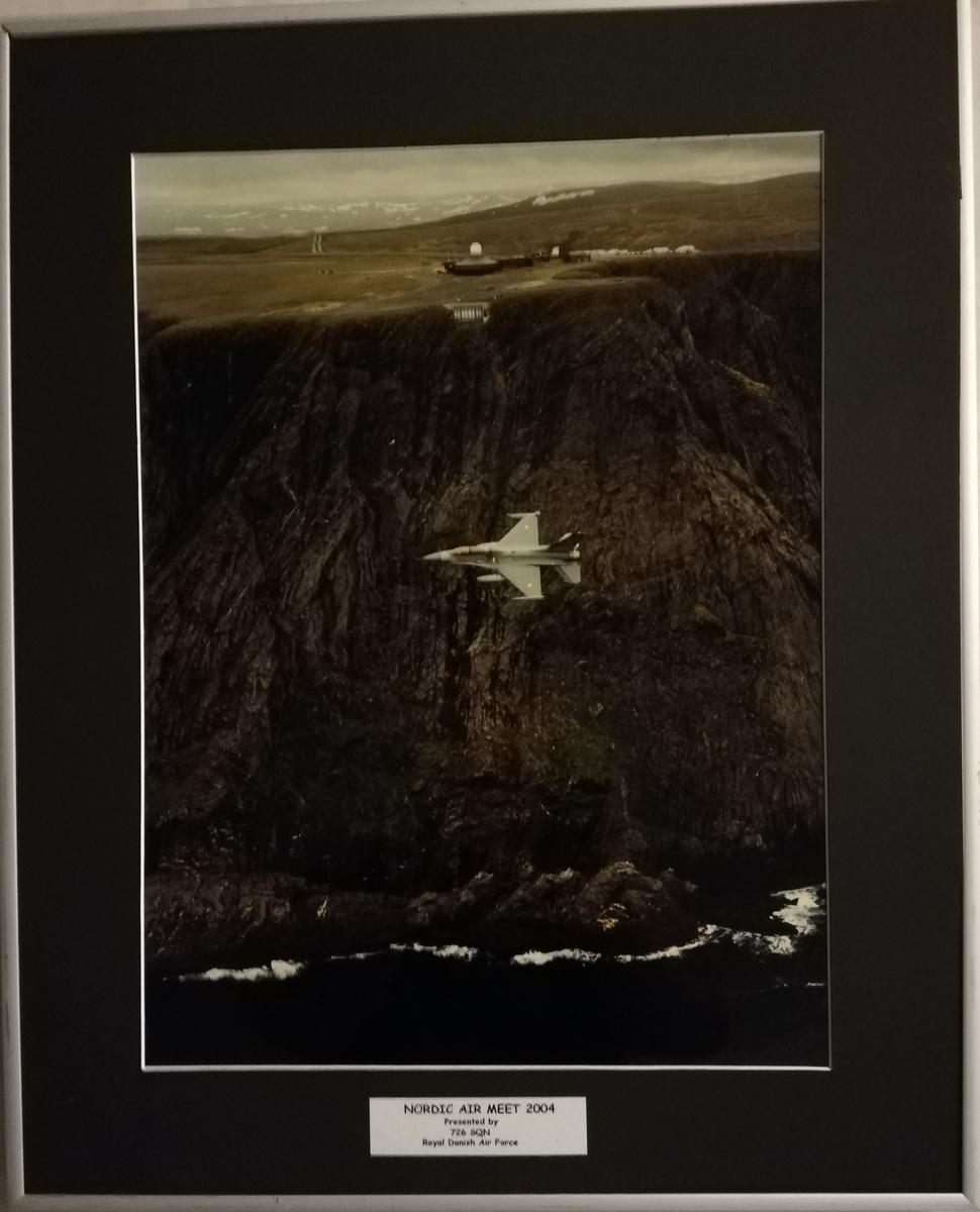 Foto av Dansk F-16 med Nordkapp platået i bakgrunn.