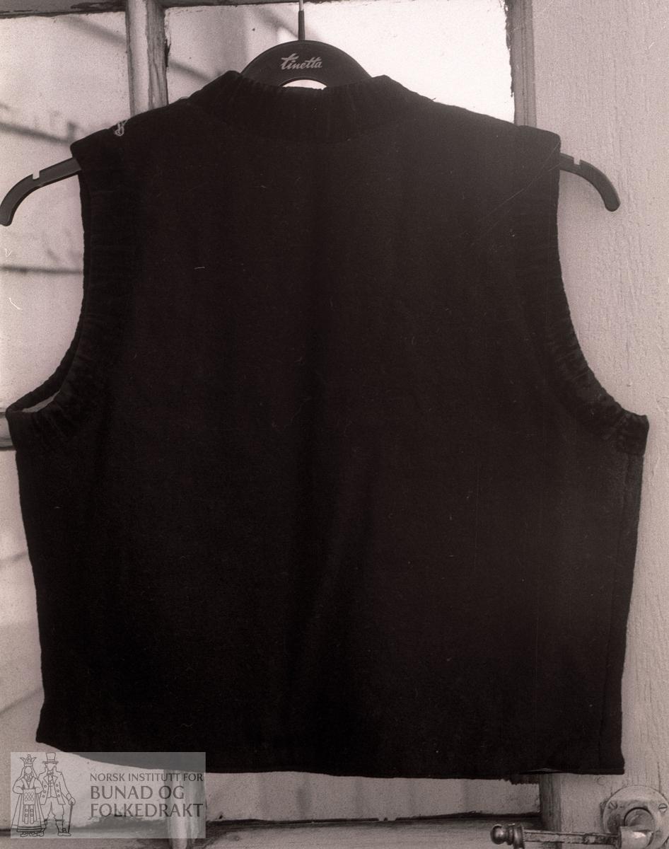 Toskaft svart, litt valka ullty, fôra med bomullslerret. Kanta med mørk grøn fløyel. H. kantar 3,2 cm. H. framkant: 36 cm. H. bak 45 cm.