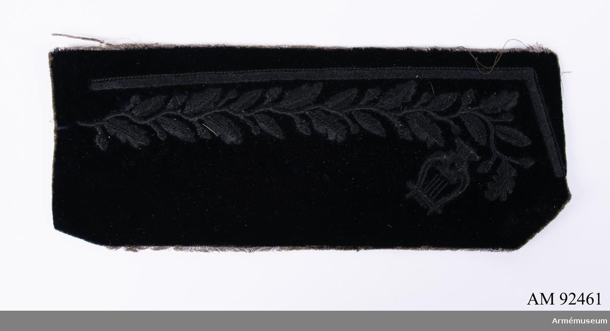 Svart kläde med svart sidenbroderi föreställande lövverk och lyra.