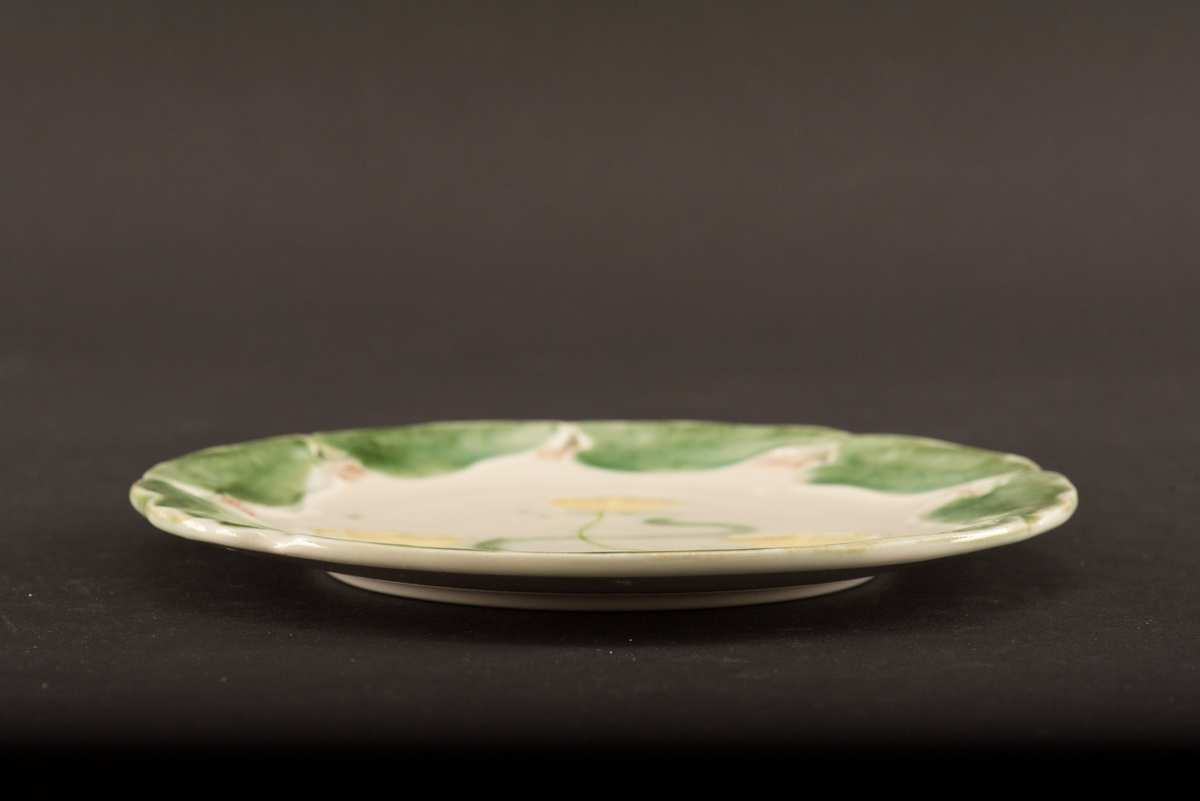 Rund assiett med dekor i relief. Brättet är i form av sju gröna näckrosblad. I mitten av fatet tre gula näckrosor. Brättet är genombrutet av sju trekantiga hål.