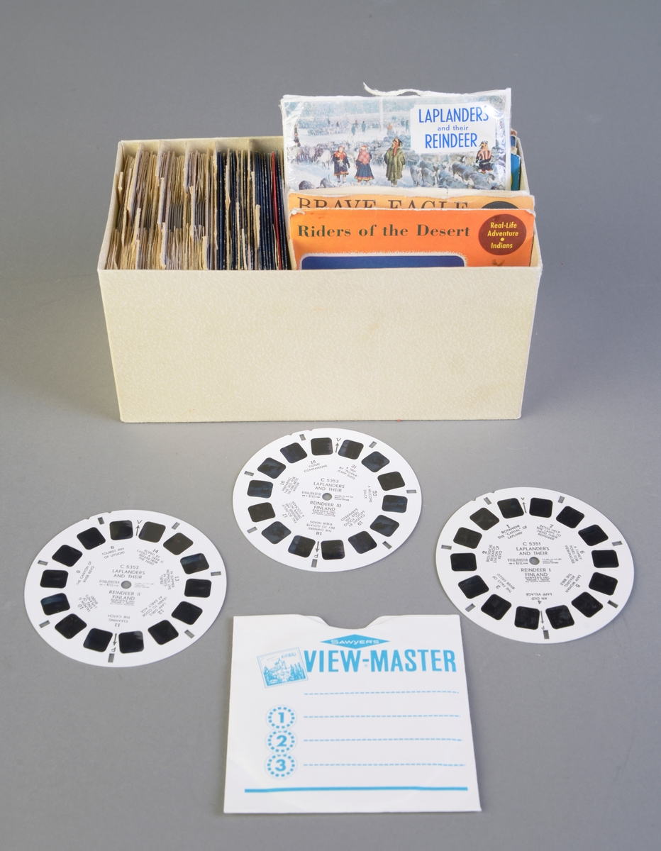 """Stereoskopsett bestående av fire deler: billedfremviseren, belysningstilsats, en eske med bildehjul og ett hefte (FTT.53896.01 - FTT.53896.04). FTT.53896.01: Viewmasteren er laget av brun bakelitt med tremønster. Bildekortene settes i en åpning på toppen av fremviseren, og på siden er det en spake man trykker ned for å få frem et nytt bilde på bildehjulet. Logoen til Sawyer er i front på fremviseren. Den ligger i originalemballasjen, og i esken ligger det en bruksanvisning og et pusseskinn fra R. Krogh i Oslo. Esken er laget av papp og er rød, svart og hvit. På esken er det tegninger av tema man kan få kjøpt som billedkort. Denne kostet 19 kroner i 1959. FTT.53896.02: Belysningstilsats til billedfremviseren laget i bakelitt med tremønster, plast og metall. I fronten er den åpen og der er det en liten lyspære. Den kan hektes på billedfremviseren i fronten og dermed gi lys til opplevelsen. Logoen er på toppen. Belysningstilsatsen ligger i originalesken er laget av papp og er rød, hvit og svart med tekst og bilde/tegning av den. Denne kostet 16 kroner i 1959. FTT.53896.03: En liten pappeske med bildehjul både med og uten originalemballasje (se """"Andre opplysninger""""). Det er i alt 76 bildehjul. De er arkivert i et hjemmelaget arkivsystem, bortsett fra de med originalemballasje som står ved siden av.  FTT.53896.04: En utgave av View-Master Nytt fra oktober 1959. Det er en oversikt over bildehjul man kan få kjøpt. Der står det også at bildehjulene koster 3,50 per stykk, og at hvert bildehjul består av 7 par stereo fargebilder med bildebetegnelse. Eller man kan få kjøpt pakker a 3 bildehjul til kroner 10 per pakke."""
