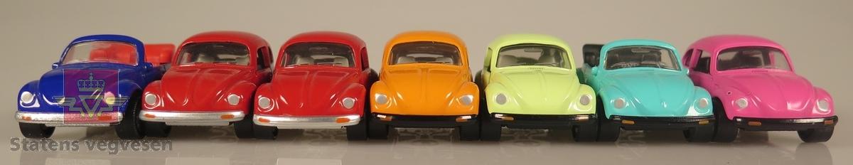 Samling av flere modellbiler. Alle er av samme produsent og produsert i lik tidslinje. 2 biler er blå, 2 biler er røde, 1 bil er grønn, 1 bil er oransje og 1 bil er rosa. Alle er laget av metall og har en skala på 1:60