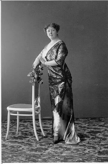 Porträtt av fru Dargel. Hon bär en lång sidenklänning, står i profil med blicken mot fotografen och lutar mot en stolsrygg. I händerna håller hon en rosbukett.