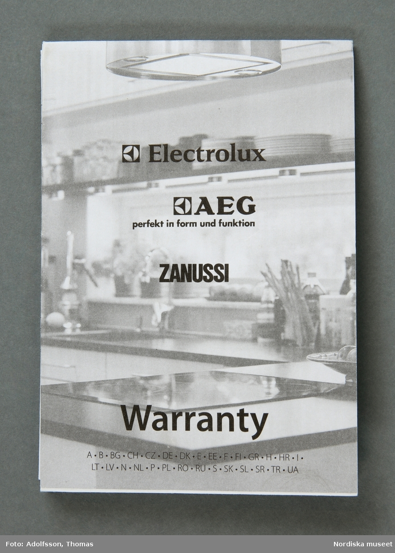 En elektrisk råsaftcentrifug av märket Elektrolux PERFECTJUICE ESF 2000. Består av  6 delar. a) Själva råsaftcentrifugen är cylinderformad och av metall och plast. De övriga delarna är av rökgrå hårdplast och består av b+) ett lock med c) press samt en d) behålllare som fruktköttet samlas i och e) en liten lockförsedd juicekanna med f) skumseparator i form av en plasskena som saften rinner ut i när den är klar. Dessutom en g) bruksanvisningsbroschyr och ett h) garantipapper. Locket (b+) har en skada där en bit är avslagen.  Lena Kättström Höök 2014-01-10