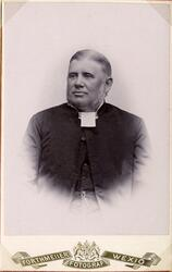 Foto av en man i prästrock och prästkrage m.m. Knäbild, halv