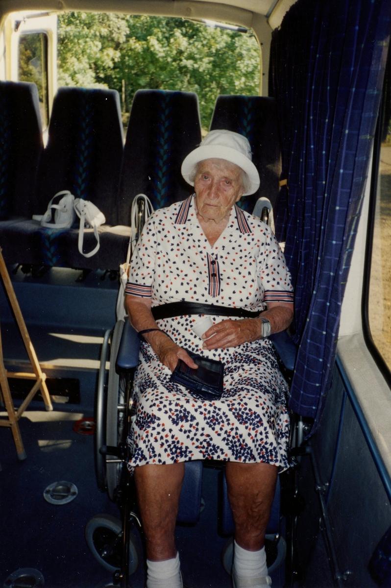 """Boende från Brattåsgårdens äldreboende är på bussutflykt till Hembygdsgården Långåker, 1990-tal. Hulda Olsson, iklädd vit hatt och svart/röd-mönstrad vit klänning (1993 - 2000). Hon sitter i en rullstol som står i bussen. Hulda var född i Vommedal Östergård """"Skräddarns""""."""
