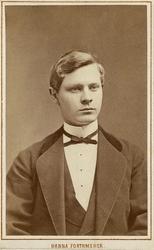 Foto av en ung man i kavajkostym med sammetskrage, väst, stä