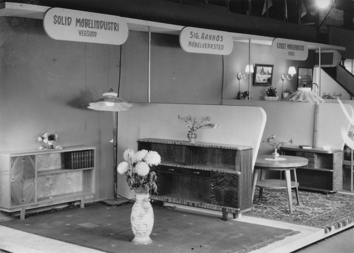 Utstilling på møbelmesse, ca år 1955. Utstillere er Solid Møbelinduistri, Vegsund, Sig. Annøs Møbelverksted, Langevåg, Gjerset Møbelverksted, Gjerset.