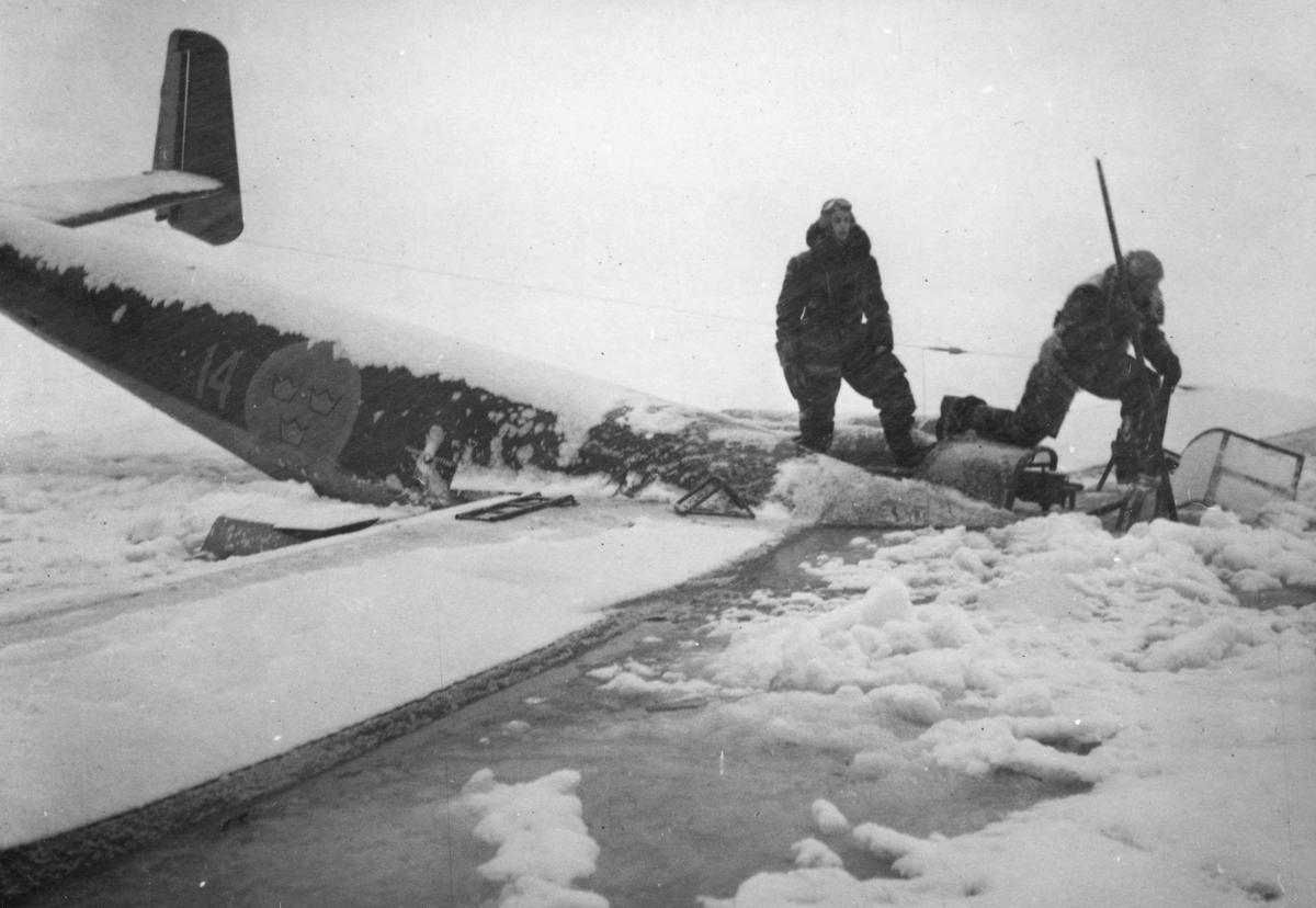 Flygplan B 18 Röd David ligger på isen utanför Härnösand efter nödlandning på isen den 10 februari 1946. Besättningen står på flygplanet.